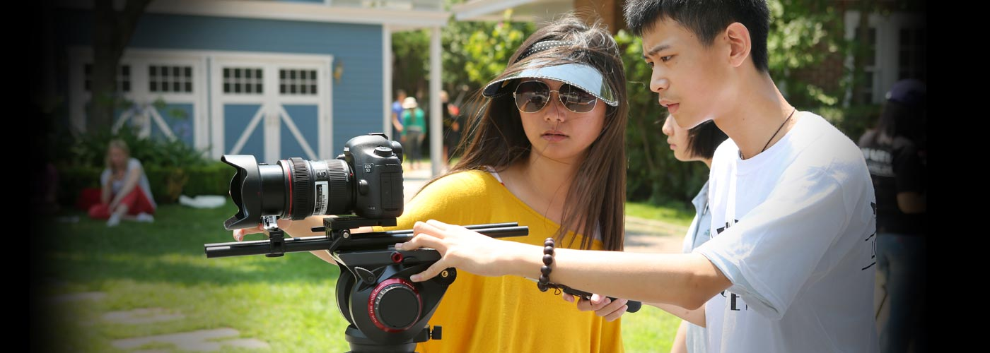 Film program students shoot with a digital camera on set
